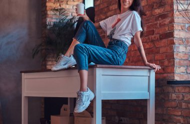 Cropped image of a cool modern girl wearing a white top and jeans sitting on a table with a cup of takeaway coffee in a studio with loft interior. stock vector