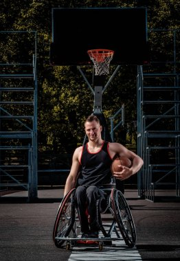 Smiling cripple basketball player in wheelchair holds a ball on open gaming ground.