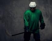 Fotografie Profesionální hokejový hráč vlaky v plné vybavení s herní holí. Na šedém pozadí, samostatný