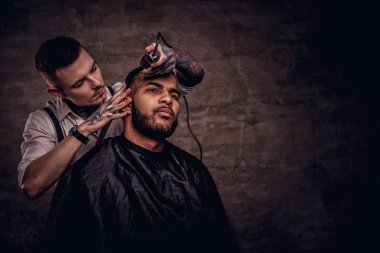 Old-fashioned professional tattooed hairdresser does a haircut to an African American client, using a trimmer and comb. Isolated on dark textured background.
