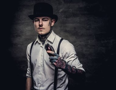 Portrait of a old-fashioned tattooed hairdresser wearing a white shirt with suspenders and cylinder hat, looking at a camera, holds a trimmer. Isolated on a dark textured background.