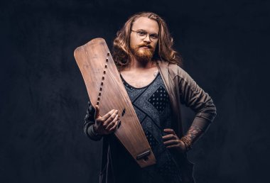 Redhead hipster male with long luxuriant hair and full beard dressed in casual clothes holds a Russian traditional musical instrument - gusli. Isolated on a dark background.