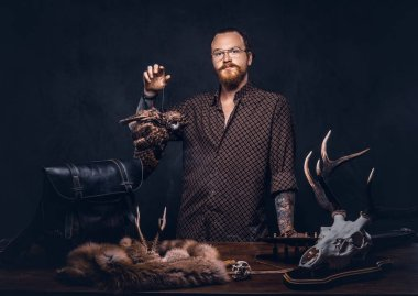 Redhead taxidermist hipster male in sunglasses dressed in a brown shirt, standing near a table with handmade trophy, owl scarecrow, and the fox skin. Isolated on a dark background.