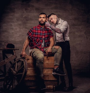 Handsome African American man getting a haircut while sitting on wooden boxes at a studio. Old-fashioned professional tattooed hairdresser does a haircut.