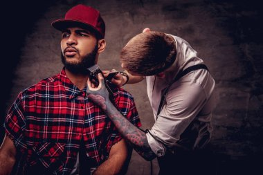Bearded African American hipster guy in a fleece shirt and cap getting a haircut by an old-fashioned professional hairdresser does haircut.