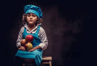 Portrait of a cute little boy with brown curly hair dressed in a blue cook uniform holds apples sitting on a wooden stool at a studio. Isolated on the dark textured background.