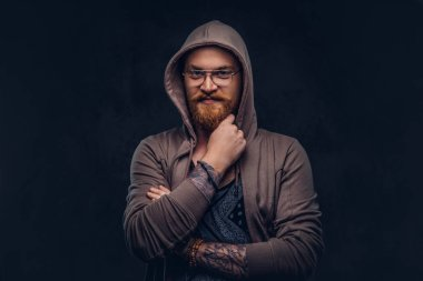 Pensive redhead hipster with full beard and glasses dressed in hoodie and t-shirt poses with hand on chin in a studio. Isolated on a dark background.
