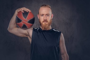 Bearded redhead basketball player in a black sportswear holding ball, isolated on a dark textured background.