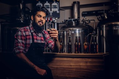 Stylish full bearded Indian man in a fleece shirt and apron holds a glass of beer, sitting behind the counter in a brewery.
