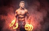 Fényképek Erős elegáns testépítő tetoválás a karján, gyakorolja a súlyzó. Tűz művészeti koncepció