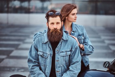 Close-up portrait of a hipster couple of a brutal bearded male and his girlfriend dressed in jeans jackets against a skyscraper.