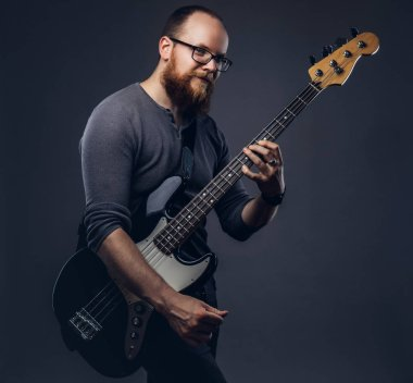 Redhead bearded male musician wearing glasses dressed in a gray t-shirt playing on electric guitar. Isolated on a gray background.