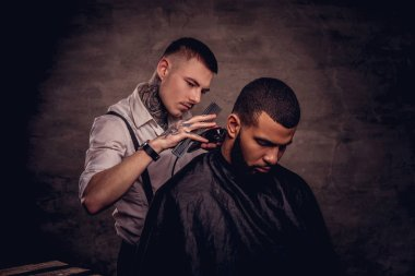 Bearded African American hipster guy getting a haircut by an old-fashioned tattoed professional hairdresser does the haircut.