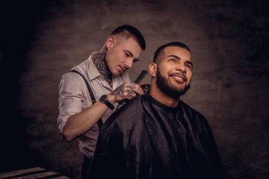 Old-fashioned professional tattooed hairdresser does a haircut to an African American client, using a trimmer and comb. Isolated on dark textured background