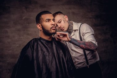 Old-fashioned professional tattooed hairdresser does a haircut to an African American client, using scissors and comb. Isolated on dark textured background.