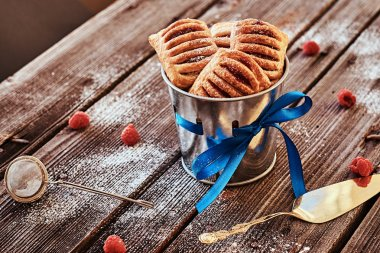 Close-up photo of a puff pastry with jam in a bucket decorated with a blue ribbon on wooden boards with raspberries and cutlery.