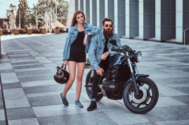 Attractive hipster couple - bearded brutal male in sunglasses and jeans jacket sitting on a retro motorcycle and his young sensual girl standing near, posing against skyscraper.