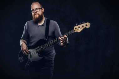 Redhead bearded male musician wearing glasses dressed in a gray t-shirt playing on electric guitar. Isolated on a dark textured background.