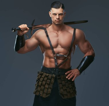 Brutal ancient Greece warrior with a muscular body in battle uniforms posing on a dark background