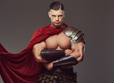 Brutal ancient Greece warrior with a muscular body in battle uniforms standing with crossed arms. Isolated on a gray background.