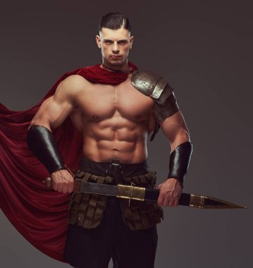 Brutal ancient Greece warrior with a muscular body in battle uniforms posing on a gray background.