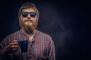 Close-up portrait of a hipster guy wearing sunglasses dressed in an old-fashioned shirt holds cup of coffee. Isolated on a dark background.