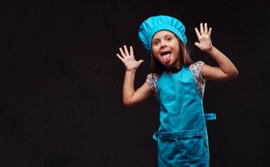 Playful little girl dressed in blue cook uniform makes faces and the pulled out tongue. Isolated on a dark textured background.