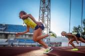 Fotografie Dvě ženské sprinter sportovci běží na běžeckém pásu závod během tréninku v atletický stadion
