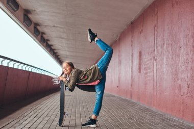 Schoolgirl with blonde hair dressed in trendy clothes dance with a skateboard at a bridge footway.
