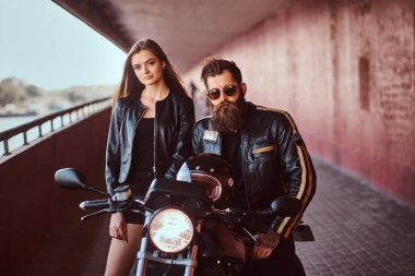 Portrait of an attractive couple - brutal bearded biker in black leather jacket with sunglasses sitting on a motorcycle and his young sensual brunette girlfriend on a footway under a bridge, looking