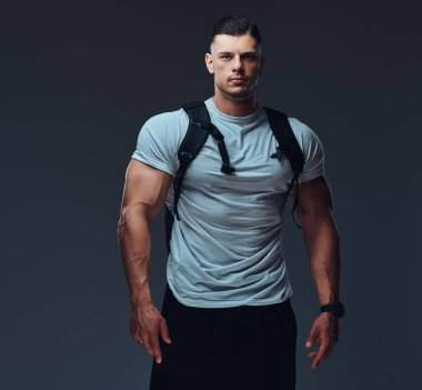 Muscular handsome bodybuilder in sportswear with rucksack posing against a gray background.