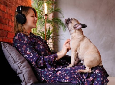 Happy blonde woman in dress playing with her cute pug and listening to music in room with loft interior.