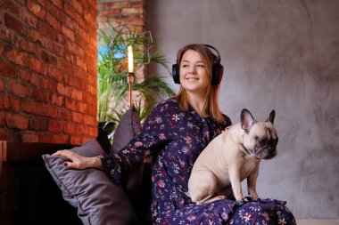 Happy blonde woman in dress sitting with her cute pug on a handmade sofa and listening to music in a room with loft interior.
