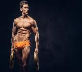 Fotografie Schöne nackte Ectomorph Bodybuilder mit stilvollen Haar in Unterhosen posiert mit einer Langhantel-Datenträger auf einem dunklen Hintergrund