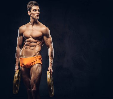 Handsome naked ectomorph bodybuilder with stylish hair in underpants posing with a barbell disk on a dark background.