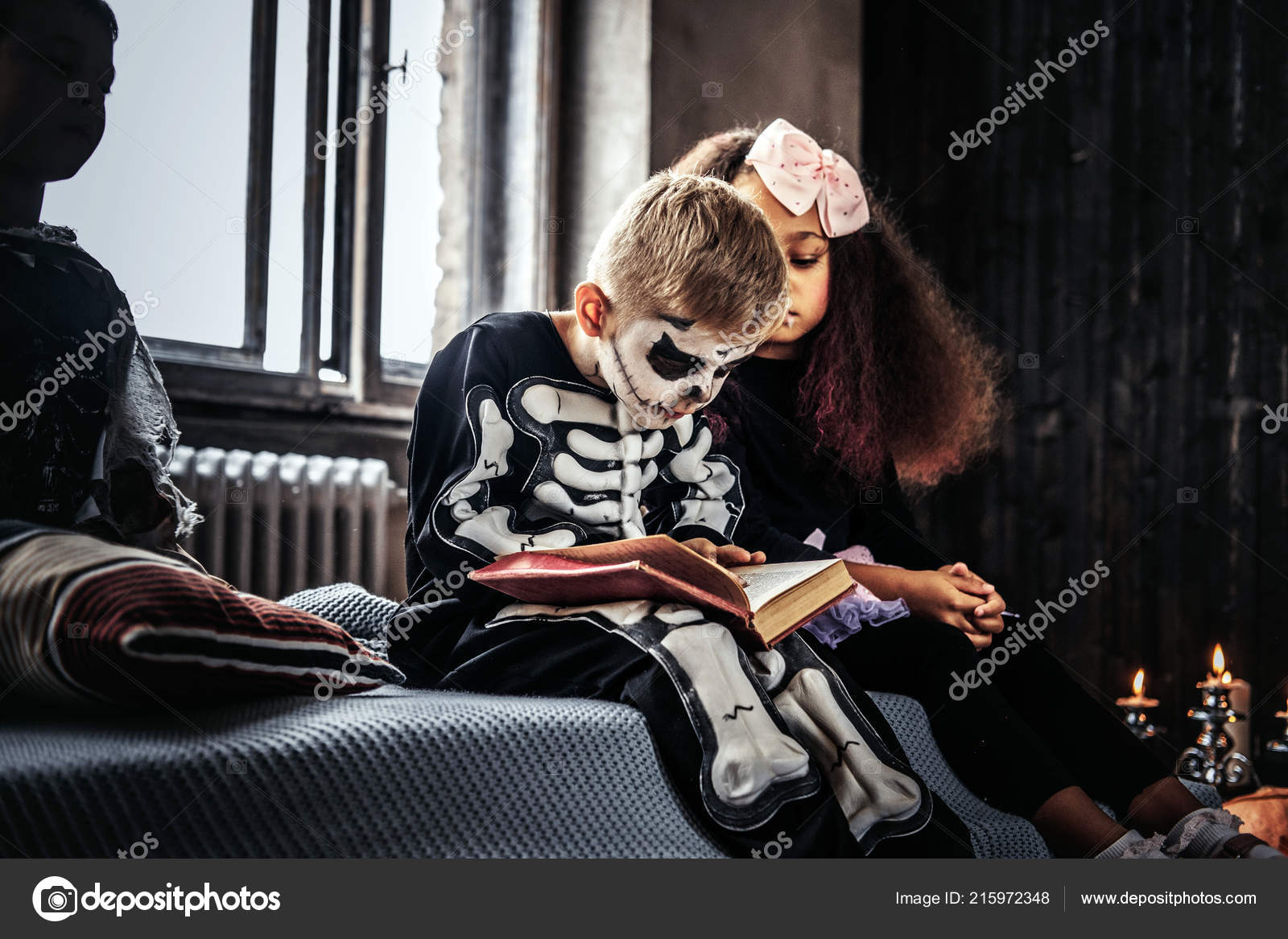 Three multiracial kids in scary costumes reading horror