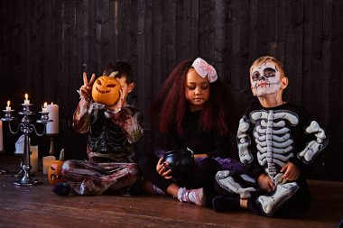 Group of cute multiracial kids in scary costumes during Halloween party in an old house.