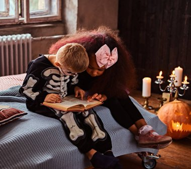 Three multiracial kids in scary costumes reading horror stories while sitting on bed in an old house.