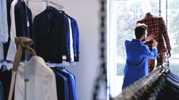 Stylový vousatý prodávající se stará o oblek na manekýně v úložišti Pánská.