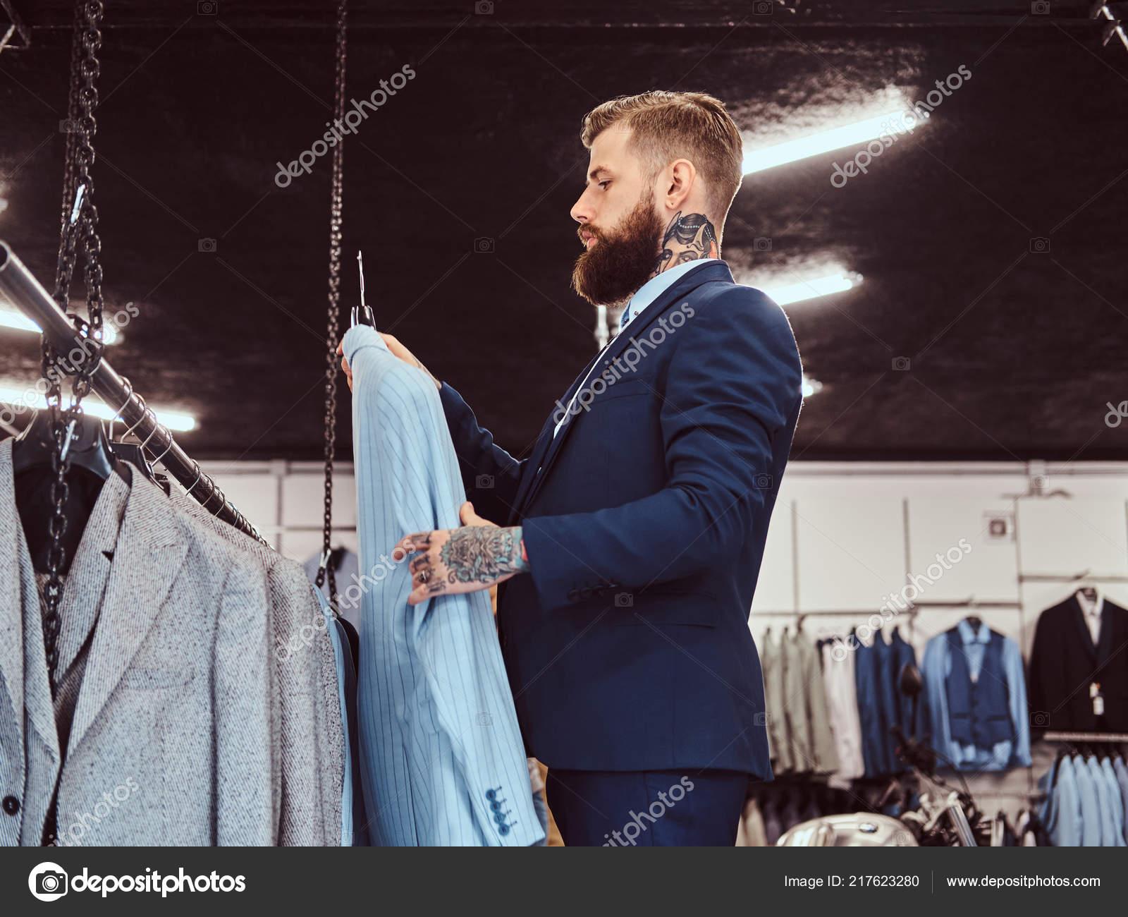 ba246f2ca1 Elegantemente vestito uomo barbuto con tatuaggi sulle mani e collo ...