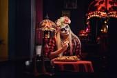 Fotografie Junge blonde Mädchen mit Untoten Make-up in Blumen Kranz Essen Nachos in einem mexikanischen restaurant.