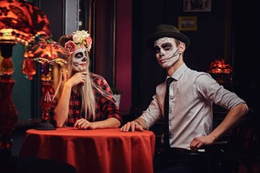 Young attractive couple with undead makeup during dating at a mexican restaurant.