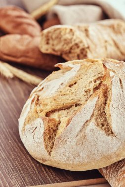Delicious freshly bakery products on wooden background. Close-up photo of a freshly baked bread products.