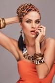 Fotografia Seducente bella donna scialle colorato sulla testa e accessori, in posa con la mano sul viso e labbra