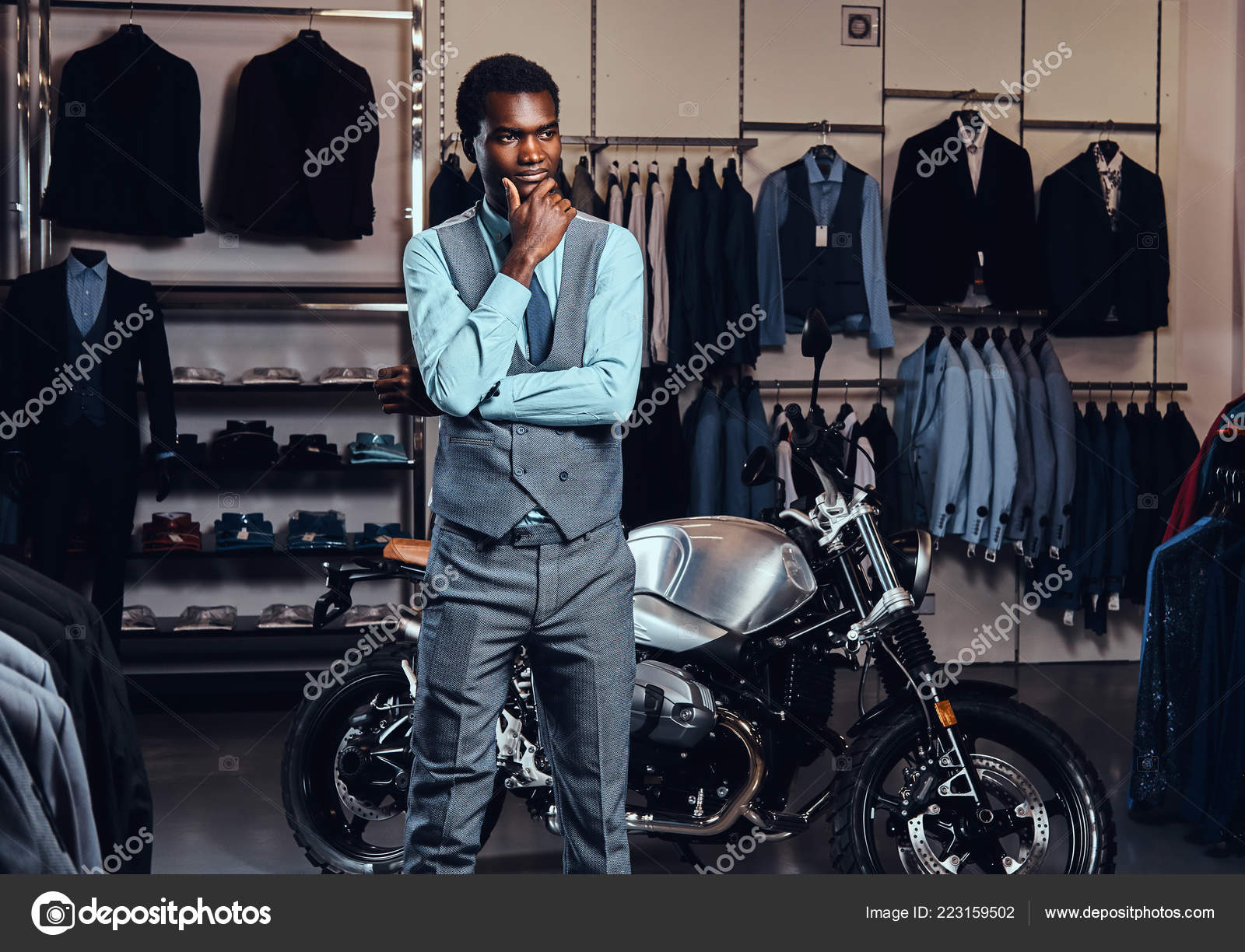 18e496f2 African American young man elegantly dressed posing near retro sports  motorbike at the mens clothing store.