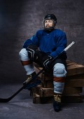 Portrait of a bearded hockey player wearing full sports equipment holding a hockey stick while sitting on wooden pallets.
