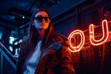 Young stylish girl wearing a hoodie coat and sunglasses standing on stairs at underground nightclub with industrial interior