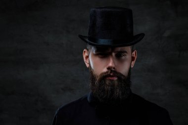 A serious old-fashioned bearded man wearing a top hat, looking at a camera, isolated on a dark background.