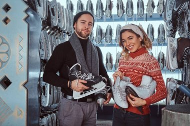Young couple wearing warm clothes standing near rack with many pairs of skates, choosing his size