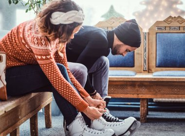 Young attractive couple sitting on a bench and tying shoelaces of ice hockey skates in the locker room